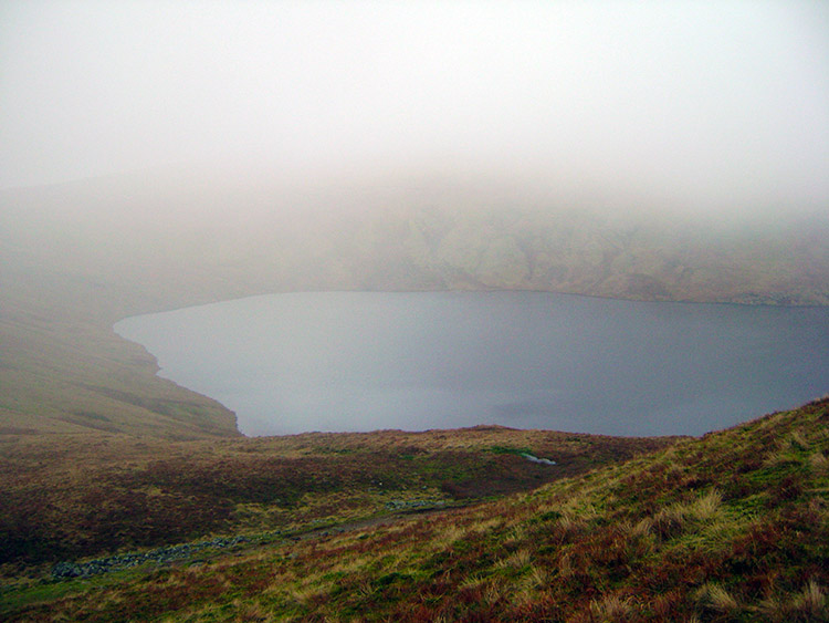 Grisedale Tarn briefly appears through the mist