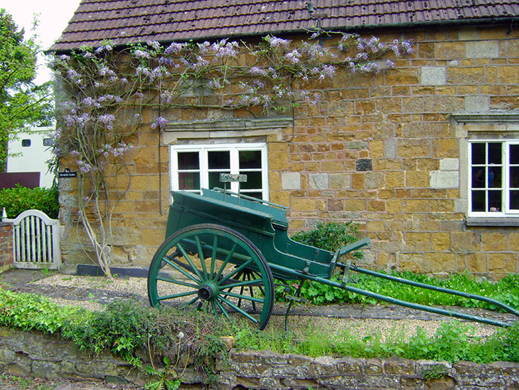 Old cart and wisteria in Burrough on the Hill